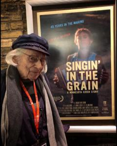 Al Milgrom poses with a poster for Singin' in the Grain